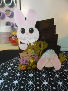 Easter Card.My take on the cascading card with the bunny in the hole. I created the ears, head, and paws with my original Silhouette,Darice wood grain embossing folders, tree canopy from Cricut, eggs,FlowerSoft for bunny tail,Spectrum Noir for colour.