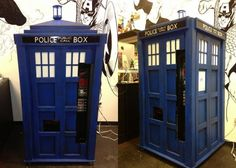 A comic book store puts a unique soda machine into service, serving up cold carbonated cans of cola from the inside of a Tardis.