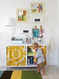 Repurposed entertainment center painted white and given adorable curtains hide supplies.