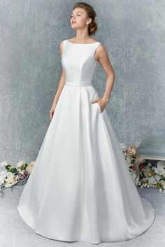 Lightweight textured satin a-line bridal gown with high neckline and pockets at the side, available off-the-rack at Silk Bridal Studio.