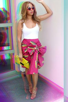 Beyonce // Stella Jean print skirt, streamlined white tank, Milli Milu yellow clutch, Azzedine Alaia studded sandals, and Quay Ohmi roung sunglasses