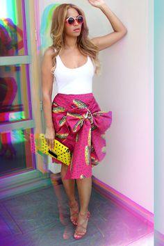 Beyoncé // Stella Jean print skirt, streamlined white tank, Milli Milu yellow clutch, Azzedine Alaia studded sandals, and Quay Ohmi roung sunglasses