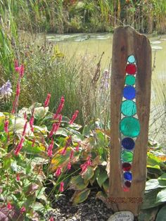 Coloured glass inset in driftwood.  Would be oh so pretty in a garden with the sun casting coloured rays all around.