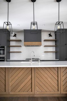 This beautiful kitchen is finished with white subway tile, black cabinets and a warm kitchen island with chevron woodwork. By Trickle Creek Custom Homes Black Kitchen Cabinets, Black Kitchens, Home Kitchens, Wooden Kitchens, Black Kitchen Countertops, Remodeled Kitchens, Black Kitchen Island, Modern Cabinets, Kitchen Islands