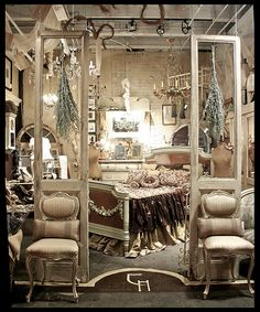 Old french doors..sans glass are used as a room divider in what looks like a display area...elegant- Elizabeth Maxson