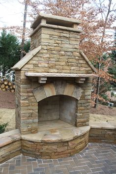 Stacked Stone Outdoor Fireplace with Seating Wall and Herringbone Paving Pattern