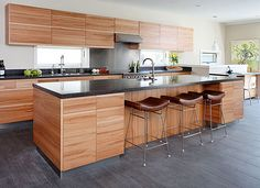 Slab full overlay doors on light color wood cabinets, dark grey countertop, lighter grey floor. Except for the prominent horizontal grain in the cabinets, these are my kitchen desires.