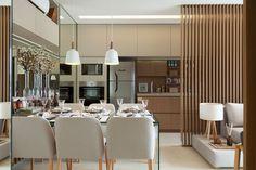Decoração de apartamento pequeno e charmoso com ambientes integrados com ripas de madeira. Na sala de jantar mesa de jantar de vidro retangular, cadeira estofada, pendente e flores.