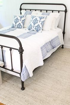 iron bed / blue and white bedding / bleached jute rug
