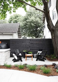 An urban Minnesota Modern backyard design, outfitted with two living spaces plus a kitchen area for a wood fired pizza oven.