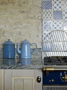 Blue, grey, taupe kitchen. Love the stone wall and blue and white tile. Very comfy and homey.