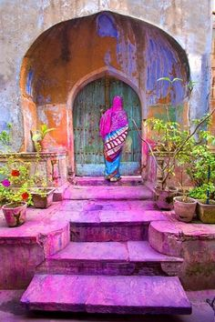 A very colorful entrance-area [ Portal ] and the door in India. The image seems to have been captured soon after the Holi color-splashing -- all that color on the steps is indicative of that.