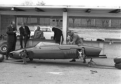 One of Peter Coltrin's great photographs: an early season testing session with the new Ferrari 156/F1 with 65° motor. The designer, Carlo Chiti, stands at the left while Enzo Ferrari, at the height of his powers, sits on the pit counter overseeing the preparations. The car, shorn of its wheels, stands like a waiting shark to take on all comers, as it would with great success. Courtesy of the Klemantaski Collection