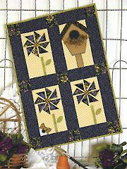 """Pinwheels & Purrs Low-Sew Quilt Pattern With 3-D prairie points that serve as the petals, pretty bumblebee centers, and a curious cat lurking in the background,   Add some embellishments to give the birdhouse and flowers some extra charm and personality. Finished size is 20"""" x 28""""."""