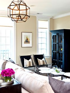 Neutral living room with browns and metals, geometric light fixture, and pink pillow