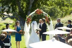 This wedding ceremony arch is decorated with tulle draping and orange and pink flowers for a golf club wedding. Photo courtesy of Magnolia Weddings Photography. Wedding ceremony flowers and event decor from Seasonal Celebrations.