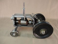 Tractor got going with pulleys from trashed weight trainer.[rear wheels] Ball bearing front wheels, electric motor parts, and other scrap stock