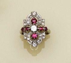 A diamond and ruby dress ring  The shaped geometric panel set with graduated single and old brilliant-cut diamonds between millegrained borders, to central claw set old brilliant between six mixed-cut rubies, white precious metal mounted, principal diamond approximately 0.25ct,