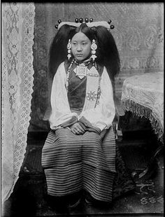 "Collection: Sir Charles Bell, Date of Photo: 1920-1921, Region: Lhasa, Aristocratic wife of Lhasa official in gala attire. The typical Central Tibetan head-dress is mainly of pearls with a few large corals; the earrings of turquoises. The charm-box ""ga'u"" (amulet box) on the chest is of gold, set with diamonds, rubies, sapphires, and turquoises'."