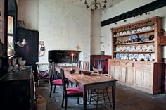 The kitchen of a Palladian-style mansion features its original flagstone flooring and fireplace. Hooks in the far corner were used for hanging meat. The Irish dresser, unlike its English counterpart, is a single piece of furniture.