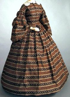 Afternoon dress ca. 1860. Brown silk with pattern of broad horizontal stripes in diamond & floral pattern, edged with cream silk. Center front closure with 15 hooks & eyes; 8 decorative buttons. Sleeves pleated at top & set in w/think piping. Pleats are fluffed & gathered, & spread out at bottom of second tier into bell shape. Skirt is of same fabric & unlined. Kentucky Historical Society
