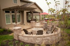 Outdoor fire pit with seating, bar area for 4 stools, built-in grill, and a covered outdoor living room