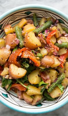 Summery Mediterranean potato salad with new potatoes, green beans, roasted red bell peppers, red onion, olives, parsley, tossed in vinaigrette. On SimplyRecipes.com