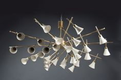 """Chandelier  Roberto Rida Italy, Contemporary Thirty white-painted aluminum shades, arranged radially on ten brass arms in sets of three, suspended from a single stem and canopy. Stamped R G RIDA on the central metal structure. Height: 22"""" Diameter: 53"""" Code : N-8913"""