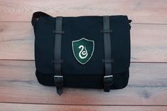 ¸,ø¤º°`°º¤ø,¸ Description ¸,ø¤º°`°º¤ø,¸ This unisex messenger bag is black with red lining and perfect for any Harry Potter fan. The house shield is made of hand-dyed and hand-painted leather, so each one is different and has small imperfections but that just adds to the handmade