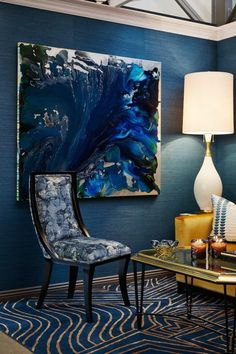 amenagement salon avec chaise fauteuil en bleu et blanc, grand panneau décoratif en nuances du bleu et du noir, table carrée avec plan doré et des pieds en métal noir, tapis aux motifs dunes en bleu marin et beige, murs en bleu canard