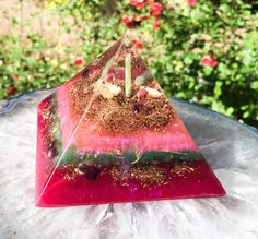 A Violet Flame Orgone heart opening crystal pyramid. Green Kyanite runs through the center of this orgonite pyramid, focusing the healing