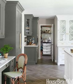 Kitchen Dreams. Swirling grays and gleaming brass warm up a classic white kitchen. Interior Designer: Caitlin Wilson. Turning a laundry room into a pantry freed up space for a desk and bar area, with cabinetry painted in Benjamin Moore's Natura in Silhouette.