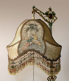 Hand-dyed Crane silk lampshade. The shade is ombre-dyed from pale gold into light jade green. The shade is covered on the sides with gold metallic mesh, silver metallic lace and the front is overlaid with metallic embroidered net. The center panels feature antique Chinese crane appliques. The shade has hand beaded fringe in golds, greens and red.