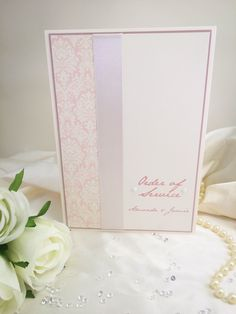 A traditional style wedding invitation with an injection of colour! A gorgeous simple knot finish on the ribbon topped with one of our favourite embellishments the Viennese pearl, simple script like font and an ornate damask style pattern. Layered on pearlised card adding a touch of sublte sparkle. An elegant choice for any wedding. #pink #blush #wedding #invitations #invites #ryanpatrickdesign #pearl #sequins #ribbon #elegant #damask #ivory…