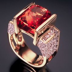 The peachy-pink 9ct Imperial Topaz is surrounded by app. 1.5 cts. of channel-set and pavé Diamonds.