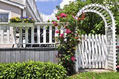 Sólido portão de jardim de madeira branca e trepadeira de rosas, com cerca também de madeira.  http://deavita.fr/design-exterieur/jardin-deco/portillon-jardin-portail/