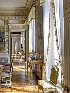 Le duplex parisien de Pierre Bergé L'enfilade. Petit salon, salle à manger, salon et entrée communiquent en enfilade. Pour unifier l'espace, Studio Peregalli a fait le choix de rideaux en voile de lin bordé de passementerie. Sur la console d'époque Louis XVI provenant du nord de l'Italie est posé un sanglier en porcelaine de Nevers et deux bougeoirs de François-Xavier Lalanne.