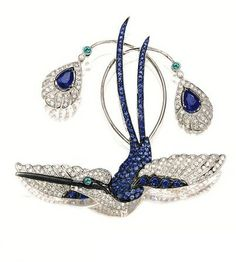 GEM-SET 'BIRD' BROOCH modelled as a bird spreading its wings, pavé-set with circular-cut sapphires and diamonds, highlighted by two pear-shaped sapphires, accented by emerald-set eye, the sapphires weighing 1.50 carats; mounted in 18 karat white gold.