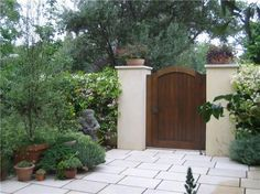 Solid wood gate hung between two stucco columns topped with plant containers. Spanish Landscaping, Outdoor Landscaping, Front Yard Landscaping, Backyard Gates, Garden Gates And Fencing, Fence Gate, Wooden Garden Gate, Wooden Gates, Wooden Fences
