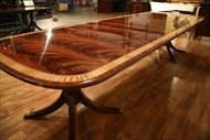 Federal style mahogany dining table with multiple extensions to seat 14 people. American made table top on custom solid mahogany Duncan Phyfe style pedestals.