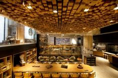 Dutch-born Liz Muller, jumps on the sustainable wagon as she taps into the reclaimed trend - walls are lined with antique Delft tiles, bicycle inner tubes, and wooden gingerbread molds; re-purposed Dutch oak was used to make benches, tables, and the undulating ceiling relief consisting of 1,876 pieces of individually sawn blocks. The design of this 4,500-square-foot space is the result of more than 35 local artists and craftsmen.