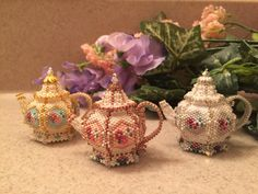 Three of my newest teapots. Made with Delica beads. Stitched bead by bead, 2 inches tall.