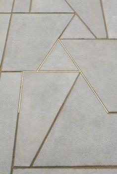 Suelo de cemento que forma dibujos geométricos, con brillantes perfiles de…