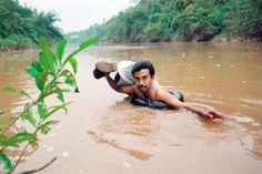Um homem de 40 anos, professor, atravessa diariamente a nado um rio na Índia para poder dar aulas