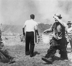"""Great Historic Photographs  Sad clown Emmett Kelly, in his performer's makeup, carrying a bucket of water in the aftermath of the Hartford circus fire of July 6, 1944, in which at least 167 people were killed. The tragedy is often called """"the day the clown cried"""" due to this photo"""