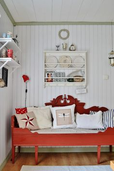 An antique Swedish pine sofa painted in traditional Swedish red is brought up to date with an eclectic collection of linen and cotton pillows.