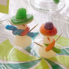 Make It: Stack two white gumdrops to make the snow people's bodies and insert a toothpick vertically down the center; top with a colored gumdrop and gummy ring to make a hat. Wrap a sour gummy worm in between the two gumdrops to make a scarf. Dip a toothpick in orange food coloring for the nose, and insert two toothpicks as arms.