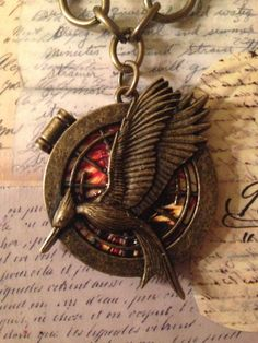 """Hunger Games Catching Fire Necklace on a 20"""" Brass chain.  It is a part of the Charming Collection by LoveEuniceDesigns, $28.00"""