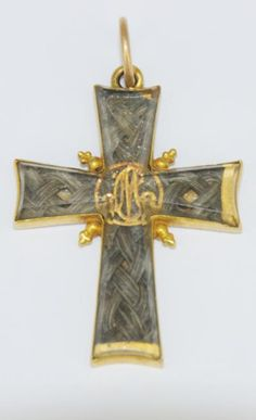 croix de deuil en or et et cheveux derrière verre