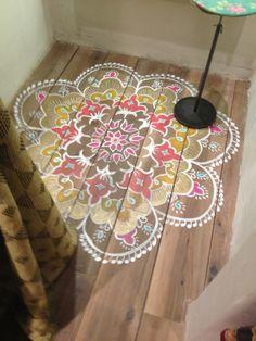 Mandala o kolam pintado sobre suelo de madera